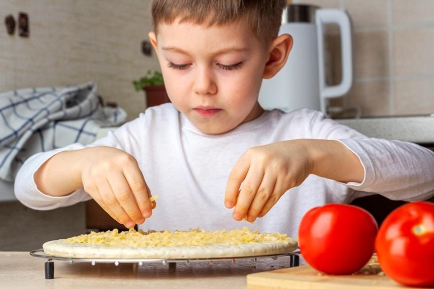 petit garçon qui fait une pizza